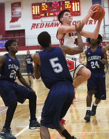 JAY YOUNG | THE GOSHEN NEWS<br /> Goshen High senior Michael Pinarski (4) finds a path to the basket between Elkhart Central defenders JT Webb (23), Kenyatta Young (25) and Michael Boone (24) during their game in the 2016 Holiday Basketball Tournament hosted by Goshen High.