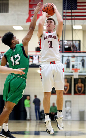 JAY YOUNG | THE GOSHEN NEWS<br /> NorthWood senior Trey Bilinski (31) puts up a guarded jumper over Concord senior Cedric Mitchell (12) during their game Thursday night in Nappanee.