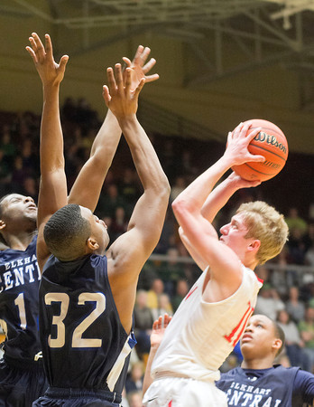 SAM HOUSEHOLDER | THE GOSHEN NEWS<br /> Goshen sophomore Brady Bechtel shoots over two Elkhart Central defenders during the 4A Sectional game Friday at Northside Gymnasium in Elkhart.