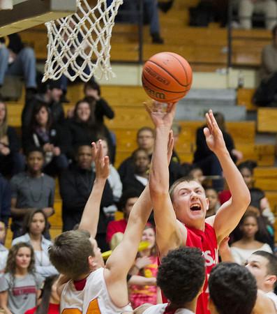 SAM HOUSEHOLDER | THE GOSHEN NEWS<br /> Goshen junior Austin Woolett shoots over Elkhart Memorial defenders during the game Friday.
