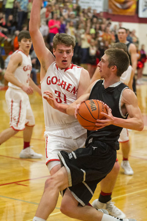 SAM HOUSEHOLDER | THE GOSHEN NEWS<br /> NorthWood senior Jonathan Wilkinson drives to the basket past Goshen defender Alex Hartsough Friday during the game.