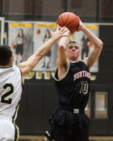 SAM HOUSEHOLDER | THE GOSHEN NEWS<br /> NorthWood senior Tanner Farmwald shoots a three pointer over a Penn defender during the game Tuesday at Penn High School.