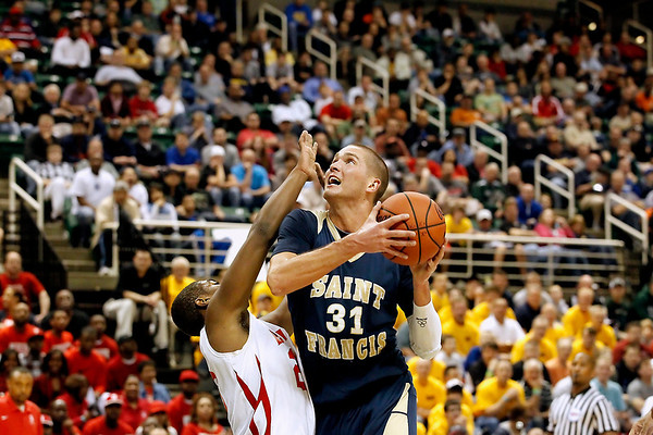 Record-Eagle/Jan-Michael Stump<br /> Traverse City St. Francis' Sean Sheldon (31) draws a foul on Flint Beecher's Markell Lucas (23) while driving to the basket in the first half of Saturday's Class C state finals in East Lansing.