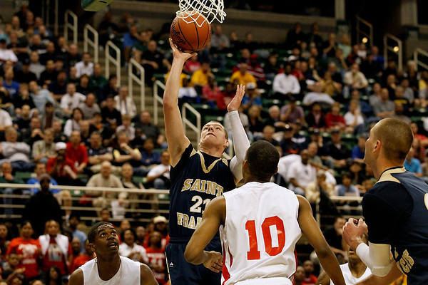 Record-Eagle/Jan-Michael Stump<br /> Traverse City St. Francis' Byron Bullough (21) shoots over Flint Beecher's Cortez Robinson (10) in the first half of Saturday's Class C state finals in East Lansing.
