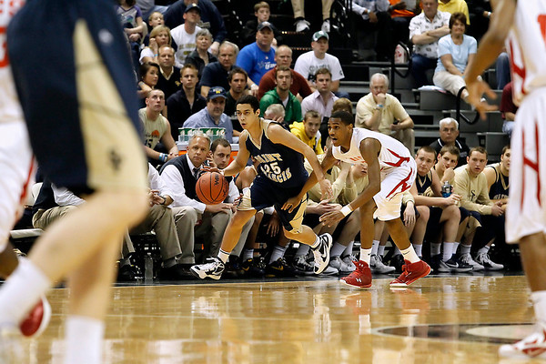 Record-Eagle/Jan-Michael Stump<br /> Traverse City St. Francis' Damon Sheehy (25) drives past Flint Beecher's Monte Morris (11) in the first half of Saturday's Class C state finals in East Lansing.
