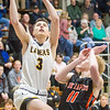 Record-Eagle/Brett A. Sommers Glen Lake guard Xander Okerlund (3) attempts a layup over Elk Rapids guard Mason Travis (11) during Wednesday's boys basketball game at Traverse City St. Francis. Glen Lake won the district semifinal 64-39.