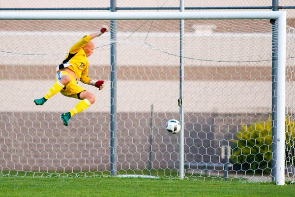 Record-Eagle/Brett A. Sommers Traverse City Central goalkeeper John Socks leaps and misses the save on a 60-yard goal by Traverse City West's Cody Miller seconds before halftime on Thursday. The Trojans and Titans drew, 2-2.