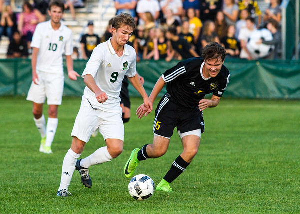Record-Eagle/Brett A. Sommers Traverse City West's Mitch Hebblewhite works the ball around Traverse City Central defender William Kunz during Thursday's match. The Trojans and Titans drew, 2-2.