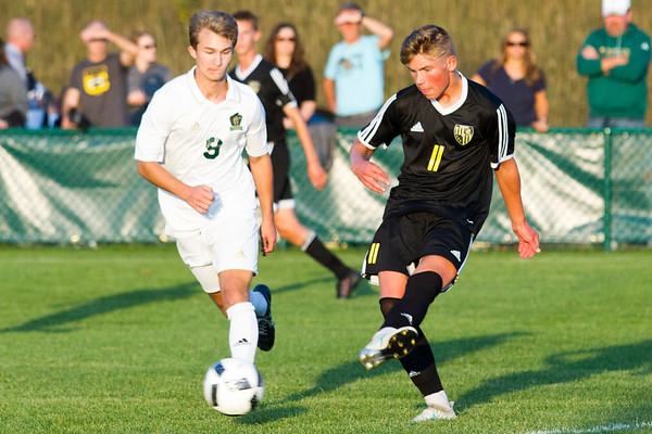 Record-Eagle/Brett A. Sommers Traverse City Central's Wiley Fraser (11) kicks the ball as Traverse City West's Mitch Hebblewhite (9) defends during Thursday's match. The Trojans and Titans drew, 2-2.
