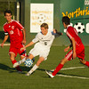 SAM HOUSEHOLDER | THE GOSHEN NEWS<br /> Northridge sophomore midfielder Nathan Blyly kicks the ball between Goshen defenders senior Kyle Ramirez Ingold (18) and junior Sebastian Flores-Cruz Tuesday during the game.