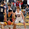 GREG KEIM | THE GOSHEN NEWS<br /> Junior Cordell Hofer of the Fairfield Falcons, No. 12, works the ball into position while being guarded by senior Brockton Yoder of the Goshen RedHawks in a high school boys basketball game Saturday night at Goshen.