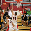 GREG KEIM | THE GOSHEN NEWS<br /> Junior Payton Faldoe of the Fairfield Falcons launches a shot over junior Bryant Robinson of the Goshen RedHawks in a high school boys basketball game Saturday night at Goshen. The RedHawks were 44-43 winners on a last-second 3-pointer by Robinson.