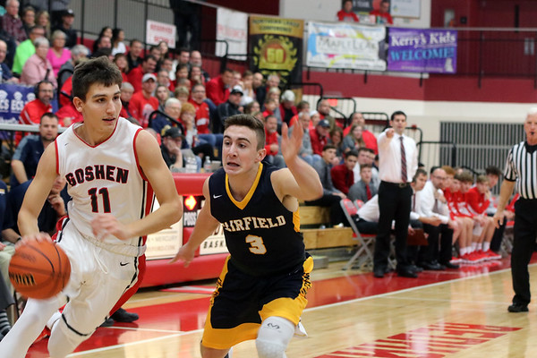 GREG KEIM | THE GOSHEN NEWS<br /> Senior Will Line of the Goshen RedHawks pushes the ball up the floor while being guarded by junior Bentley Miller of the Fairfield Falcons in a high school boys basketball game Saturday night at Goshen.
