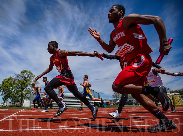 JAY YOUNG | THE GOSHEN NEWS<br /> Elkhart Memorial's Wisdom Chigwada takes the baton from a teammate while staying out in front of Fort Wayne North Side's Michael Clack (1586) as they compete in the 4x100 relay during the 75th running of the Goshen Relays Saturday at Goshen High School.