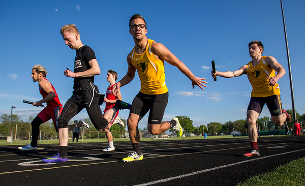 JAY YOUNG | THE GOSHEN NEWS<br /> Northridge's Brad Schwartz reaches behind to receive the baton from Brody Long as they race in the 4x100 relay at the 47th annual Kelly Relays Friday evening at Concord High School.