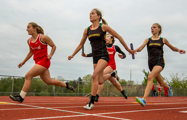JAY YOUNG | THE GOSHEN NEWS<br /> Northridge's Emily Wargo takes the baton from teammate Shelby Heerschop at the first handoff in the 4x100 relay during the Norther Lakes Conference Championship track meet Tuesday evening in Warsaw.