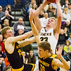 Record-Eagle/Brett A. Sommers Glen Lake's Cade Peterson (23) muscles through Iron Mountain's Charlie Gehrard (44) and Jacob Tucker (30) during Tuesday's Class C boys basketball quarterfinal at Petoskey High School. Glen Lake won 66-49.