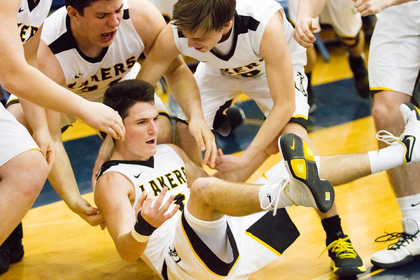Record-Eagle/Brett A. Sommers Glen Lake's Peyton McDonough (center) is surrounded by teammates after hitting a third-quarter buzzer beater during Tuesday's Class C boys basketball quarterfinal against Iron Mountain at Petoskey High School. Glen Lake won 66-49.