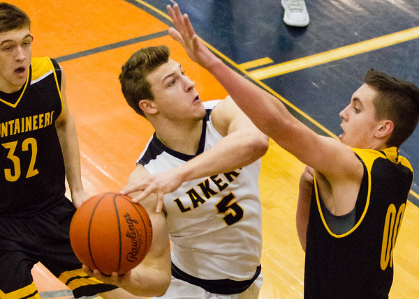 Record-Eagle/Brett A. Sommers Glen Lake's Nick Apsey (5) takes the ball to the basket against Iron Mountain's Foster Wonders (00) during Tuesday's Class C boys basketball quarterfinal at Petoskey High School. Glen Lake won 66-49.