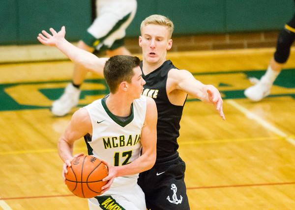 Record-Eagle/Brett A. Sommers Glen Lake's Cade Peterson defends McBain's Garrett VerBerkmoes during Monday's Class C regional semifinal at Houghton Lake High School. Glen Lake won 66-32.