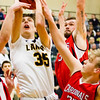 Record-Eagle/Brett A. Sommers Glen Lake's Reece Hazelton shoots over three Whittemore Prescott players, including Michael Blust (33) during Wendesday's regional championship boys basketball game at Houghton Lake High School. Glen Lake won 75-46.