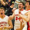 Record-Eagle/Brett A. Sommers Manton's Preston Shazri (left), Jacob Teed (middle) and Caleb Teed (right) celebrate from the bench during Wednesday's regional championship game against Boyne City in Houghton Lake. Manton won 47-46.