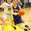 Record-Eagle/Brett A. Sommers Traverse City St. Francis' Mitch Lurvey dribbles by Glen Lake's Reece Hazelton during the first half of Friday's district championship game. Glen Lake won 61-33.