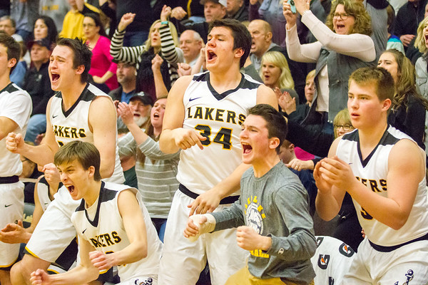Record-Eagle/Brett A. Sommers Glen Lake's bench celebrates amidst the Lakers' 20-0 run to start the third quarter during Friday's boys basketball district championship against Traverse City St. Francis. Glen Lake won 61-33.