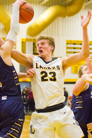 Record-Eagle/Brett A. Sommers Glen Lake's Cade Peterson fights for a rebound during Friday's boys basketball district championship against Traverse City St. Francis. Glen Lake won 61-33.