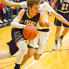 Record-Eagle/Brett A. Sommers Traverse City St. Francis' Mitch Lurvey dribbles by Glen Lake's Xander Okerlund during the first half of Friday's district championship game. Glen Lake won 61-33.