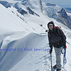 girl alpinist at the top of a knife edge ridge with rope, crampons and ice axe