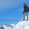 girl climber on the summit of a sheer mountain equipped with ice axe, rope, crampons and harness