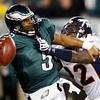 Philadelphia Eagles' Donovan McNabb, left, is sacked by Denver Broncos' Elvis Dumervil in the second half of an NFL football game, Sunday, Dec. 27, 2009, in Philadelphia. Philadelphia won 30-27. (AP Photo/Mel Evans)