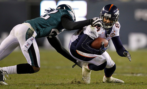 Denver Broncos' Brandon Lloyd, right, has his facemask grabbed by Philadelphia Eagles' Asante Samuel in the second half of an NFL football game, Sunday, Dec. 27, 2009, in Philadelphia. Philadelphia won 30-27. (AP Photo/Matt Slocum)
