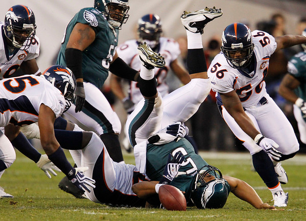 Philadelphia Eagles' Donovan McNabb, center, fumbles the football as he is sacked by Denver Broncos' Elvis Dumervil in the first half of an NFL football game, Sunday, Dec. 27, 2009, in Philadelphia. (AP Photo/Matt Slocum)