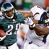 Philadelphia Eagles' LeSean McCoy, left, tries to break a tackle from Denver Broncos' Robert Ayers in the first half of an NFL football game, Sunday, Dec. 27, 2009, in Philadelphia. (AP Photo/Michael Perez)