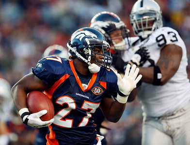 Denver Broncos rookie running back Knowshon Moreno (27) runs with the ball around the corner as Oakland Raiders defensive tackle Tommy Kelly (93) defends in the third quarter of an NFL football game in Denver on Sunday, Dec. 20, 2009. (AP Photo/David Zalubowski)