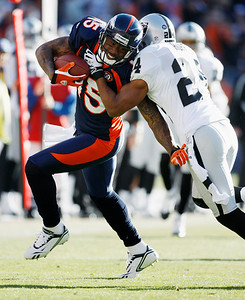 Denver Broncos wide receiver Brandon Marshall (15) is tackled by Oakland Raiders safety Michael Huff after Marshall pulled in a pass in the first quarter of an NFL  football game in Denver on Sunday, Dec. 20, 2009. (AP Photo/Jack Dempsey)