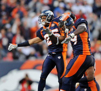 Denver Broncos' Vonnie Holliday, right, and Tony Carter celebrate in the third quarter after Carter recovered an  Oakland Raiders' fumble during an NFL  football game in Denver on Sunday, Dec. 20, 2009. (AP Photo/Chris Schneider)