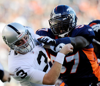 Denver Broncos' Mario Haggan hits Oakland Raiders quarterback Charlie Frye in the first quarter of an NFL football game in Denver on Sunday, Dec. 20, 2009.  (AP Photo/Chris Schneider)