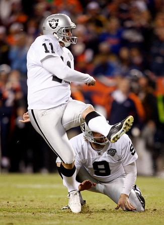 Oakland Raiders place kicker Sebastian Janikowski (11) watches as the ball splits the uprights for a go-ahead extra point as Shane Lechler (9) holds during the fourth quarter of an NFL football game against the Denver Broncos at Invesco Field at Mile High in Denver, Sunday, Dec. 20, 2009. Oakland defeated Denver 20-19. (AP Photo/Jack Dempsey)