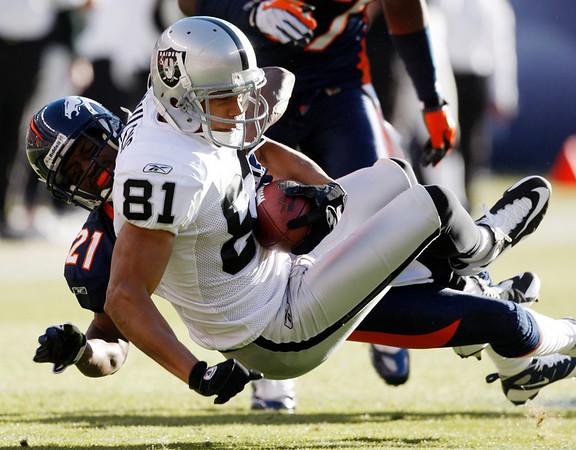 Oakland Raiders' Chaz Schilens (81) pulls in a pass as Denver Broncos' Andre' Goodman (21) defends on the play during the first quarter of an NFL  football game in Denver on Sunday, Dec. 20, 2009. (AP Photo/Jack Dempsey)