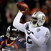 Oakland Raiders quarterback JaMarcus Russell (2) throws a pass during the fourth quarter as Denver Broncos' Robert Ayers, left, applies pressure during an NFL football game in Denver on Sunday, Dec. 20, 2009. (AP Photo/Chris Schneider)