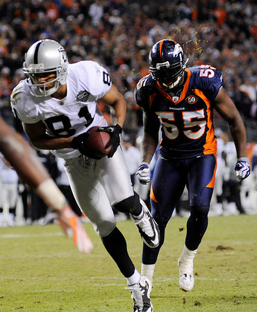 ** CORRECTS TO GAME-TYING TOUCHDOWN INSTEAD OF GO-AHEAD TOUCHDOWN ** Oakland Raiders wide receiver Chaz Schilens runs past Denver Broncos' D.J. Williams (55) for the game-tying touchdown on a 10-yard pass reception in the fourth quarter of an NFL football game in Denver on Sunday, Dec. 20, 2009.  The Raiders won 20-19. (AP Photo/Chris Schneider)