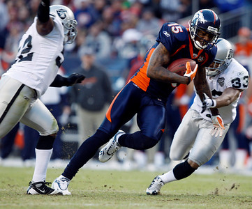 Denver Broncos wide receiver Brandon Marshall, center, pulls in a pass between Oakland Raiders linebacker Kirk Morrison, left, and safety Tyron Branch in the third quarter of an NFL football game in Denver on Sunday, Dec. 20, 2009. (AP Photo/David Zalubowski)