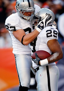 Oakland Raiders running back Michael Bush (29) is congratulated by teammate Brandon Myers (83) after running for a touchdown during the second quarter of an NFL football game against the Denver Broncos at Invesco Field at Mile High in Denver, Sunday, Dec. 20, 2009. (AP Photo/Jack Dempsey)