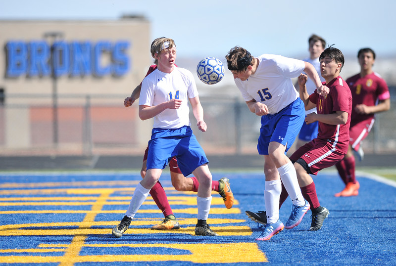 Tibby McDowell | The Sheridan Press<br /> Chance Quarterman (14), left, blocks Laramie on a corner kick as Sam Smart (15) attempts to head the ball in for a goal at Homer Scott Field Saturday, March 24, 2018. The Broncs had a scoreless draw with the Plainsmen in a two overtime match.