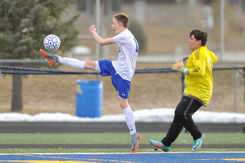 Tibby McDowell | The Sheridan Press<br /> Carter Wells high kicks the soccer ball to keep it inbounds at the goal line during the first home game against Cheyenne South at Homer Scott Field Friday, March 23, 2018.
