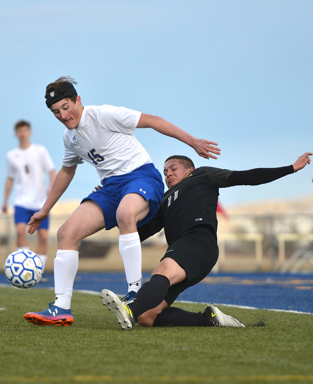 Justin Sheely | The Sheridan Press<br /> Sheridan's Sam Smart, left, passes the ball against Cheyenne South's Zeuss Jimenez at Homer Scott Field Friday, March 23, 2018. The Broncs fell 3-1.