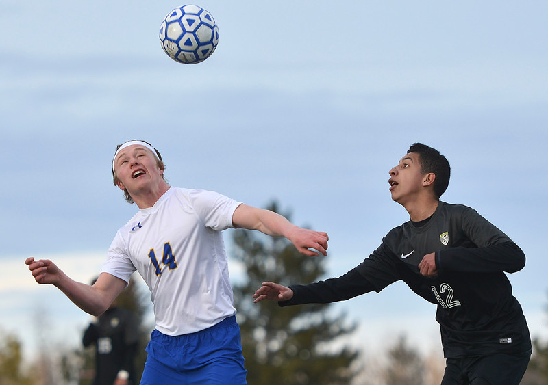 Justin Sheely | The Sheridan Press<br /> Sheridan's Chance Quarterman (14) takes a header over Cheyenne South's Pablo Sanchez at Homer Scott Field Friday, March 23, 2018. The Broncs fell 3-1.